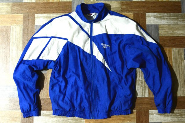 <img class='new_mark_img1' src='https://img.shop-pro.jp/img/new/icons5.gif' style='border:none;display:inline;margin:0px;padding:0px;width:auto;' />90's Vintage Reebok ビッグロゴ ナイロン トラック ジャケット ブルー (メンズ古着)