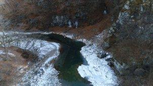 冬 山の中を流れる川 川面に沿って低空飛行