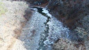 冬 山の中を流れる川 上空から川面へ