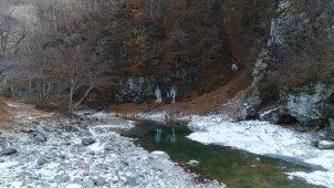 冬 山の中を流れる川 川面から上空へ