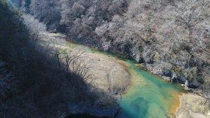 冬 山の中を流れる川 光る水面