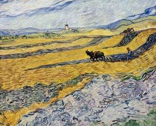 耕す人と風車のある畑