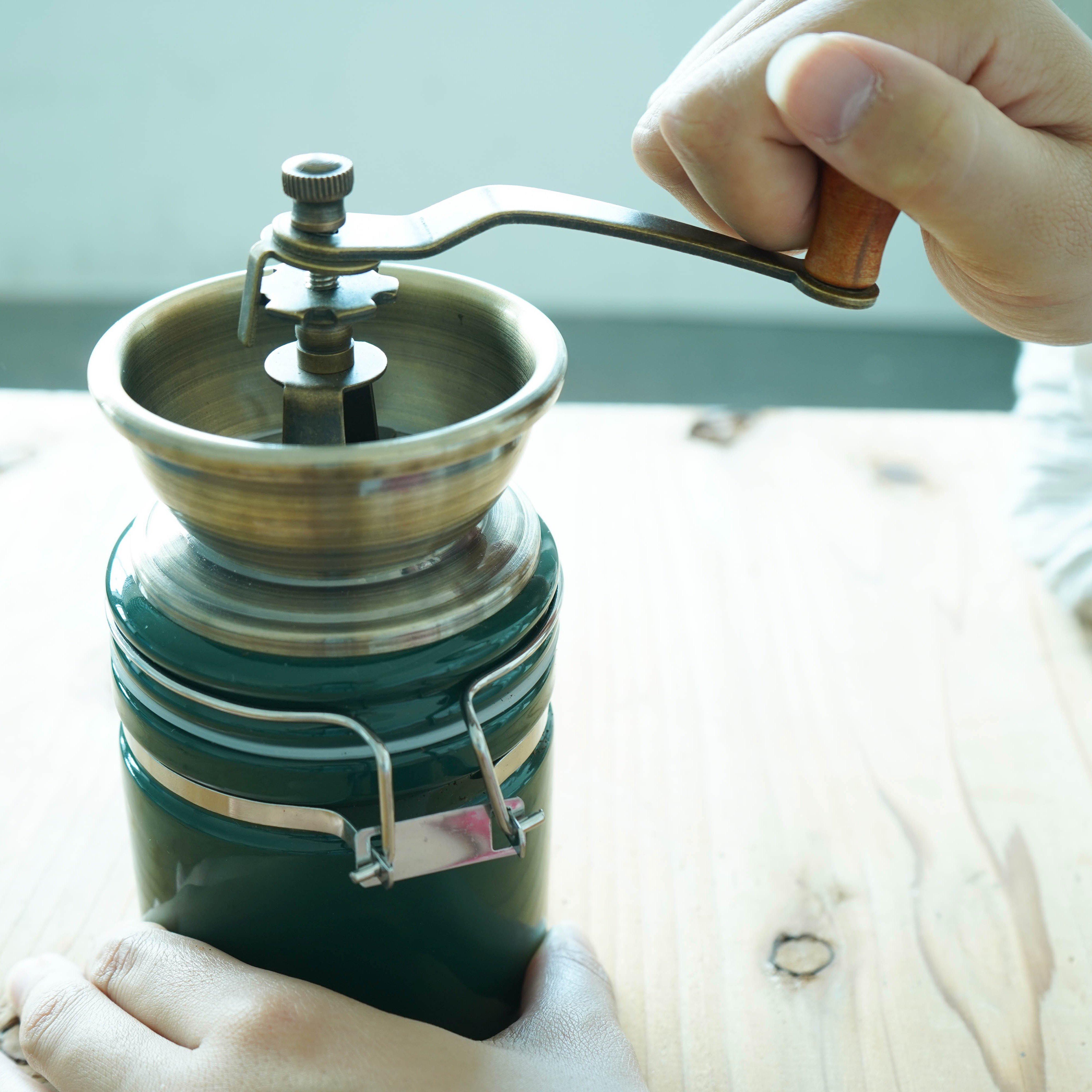 ヴィンテージデザインで おしゃれな手挽きのコーヒーミル     グラインダーは臼式で、均一に粉にできます。さらに、お手入れが簡単なセラミック素材です。  細挽き、粗挽き調整は無段階調整で可能。  ロック式の受け容器なので、しっかりロックして豆を挽くことができます。挽いている間に豆がこぼれたりすることもなく、また挽きたての香りを逃さず美味しいコーヒーを味わうことができます。  引き目の調整やお手入れも非常に簡単です。(説明書付き)     挽いたあとはワンタッチ金具を外して粉を取り出せます。    引き目も金具の締め方で浅煎り~深煎りまで自由に調整できます。    【スタッフからの一言】 豆は香りのカプセル。やはり挽きたてのコーヒーは本当に香りまで美味しいです。 ガリガリと手で挽くひと手間が、手挽きミルの醍醐味。 味わいのあるミルをぜひ使い込んでみてください。    【商品について】 サイズ(mm) :H22cm × W15.5cm × D8cm 容量      :コーヒー豆100g(満杯時受け容器) 本体      :アイアン、ニッケルメッキ  受け容器    :ストーンウェア、シリコン グラインダー  :セラミック ハンドル    :アイアン、バーチウッド