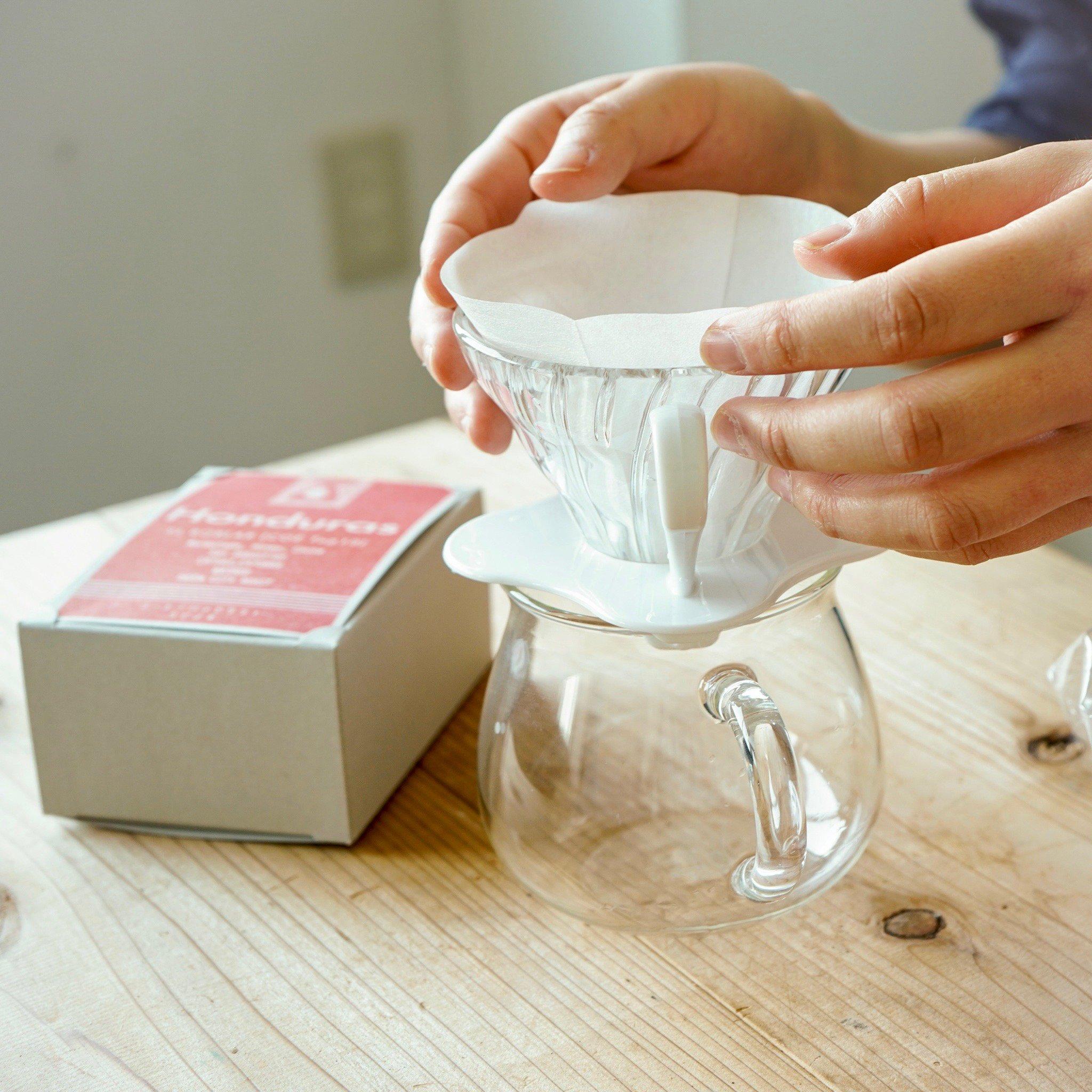 さぁ、コーヒーを始めよう    ▷内容 ①HARIO V60 耐熱ガラス透過ドリッパー01W ②SLOW COFFEE STYLE コーヒーサーバー 300ml ③HARIO V60ペーパーフィルター01W 100枚 ④ホンジュラス エルロブラル農園(COE入賞)150g  コーヒーは人や淹れ方によって味が変わるもの。 その時々の気分やシーンに合わせて、好みのコーヒーを淹れる。 自分のためでも良いし、大切な誰かのためでも良い。  タビノネのスタッフが「使ってみて良かった!」と自信をもっておすすめできるコーヒー器具たちを集めました。    ハンドドリップに必要なドリッパー・コーヒーサーバー・フィルター・コーヒー豆の4点セットです。 ハンドドリップをこれから始めたい方におすすめのセットです。     ▷詳細 ①V型円すい形のペーパーフィルター 珈琲粉の層が深く、珈琲粉に注いだお湯が円すいの頂点に向かって流れるので豆の旨味をしっかりと抽出できます。 透明の耐熱ガラス製なので、コーヒーを抽出する間も様子が見え、目でコーヒーを楽しむことができます。  ②キントーコーヒーサーバー ゆるやかなフォルムや落ち着いた色合い、あたたかみのあるデザインが心をほぐします。 ポットには抽出量が分かる目盛りがデザインされています。  ③V60シリーズペーパーフィルター01タイプ 材質はパルプ100%の酸素漂白仕様。環境にやさしい森林認証制度FSCを取得した製品です。  ④ホンジュラスエルロブラル 蜂蜜のような奥深い甘みがあり、スイーツを食べているかのような甘い余韻が残ります。 中深煎りですので苦味は少なく、果実感と甘みの余韻をお楽しみ頂けます。  【お届けに関して】 ラッピングはしておりません。 紙袋をご利用希望の方は選択欄にてご記入ください。
