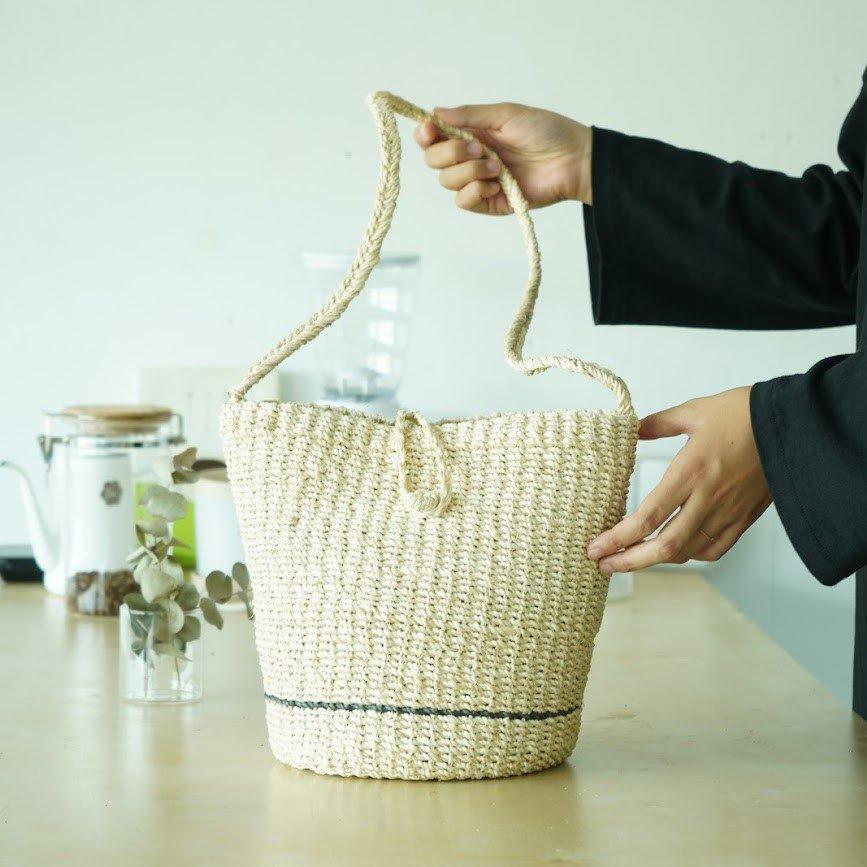 バッグから夏をはじめる    持つだけでコーデをぐっと夏らしく演出してくれるマニラ麻を使った天然素材の「かごバック」。 普段のコーデに取り入れるだけで、季節感あふれるスタイルに仕上がる便利なアイテムです。    春夏らしいアバカ素材を使用したショルダーバッグ。 一筋入ったポイントカラーはナチュラルな雰囲気にピッタリ合います。 コロンと可愛らしい見た目ですが、丸底でしっかりとマチがあるので小ぶりながら身のまわりの物はしっかりおさまります。    財布やスマホ、鍵など必需品だけを入れてちょっとそこまでという時にもちょうどいい大きさです。 普段使いはもちろん、チョットしたお出掛けや旅行、ビーチシーンにも活躍間違いなし。  【スタッフからの一言】  日差しが照り付ける、暑い季節になってきました。 今年は一段と強い暑さを感じる気がしております。 外に出るのが億劫になりがちですが、お気に入りの服とカバンで少し気分をあげてみるのも良いかもしれません。 シンプルな服装やナチュラルな雰囲気にぴったりのかごバッグ。 この夏に涼しさを感じられるスタッフイチオシの一品です。  【商品について】  生産地:フィリピン サイズ:φ20(TOP)×H24cm(持ち手の長さ87cm) 素材:天然草木(マニラ麻) ブランド:Viva La Vida